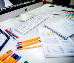 desk with mac book, pens and paper designs